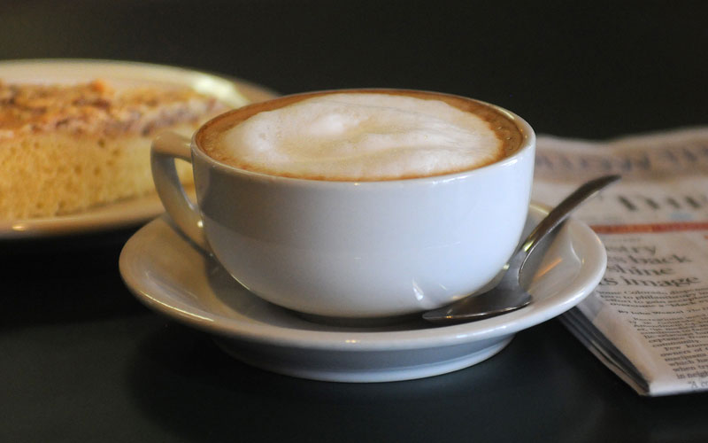 A Fika cappuccino sitting on a table with a pastry in the background.